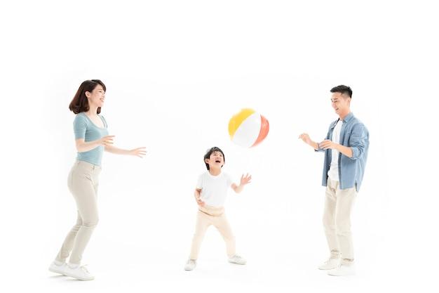 Family of three playing beach ball