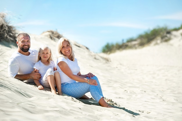 A family of three sit on the sand dunes near the town of nida.lithuania