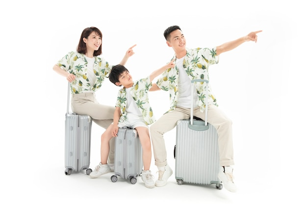 Family of three travelling sitting on suitcase