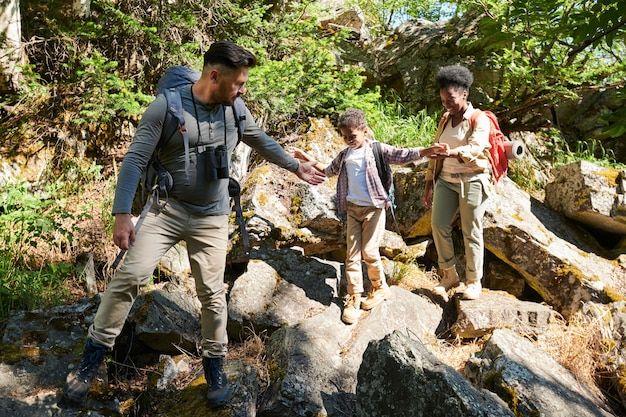 Family of three walking on big rocks they travelling in the wild nature