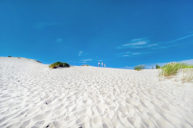 A family of three walks on the sand dunes near the town of nida.lithuania.