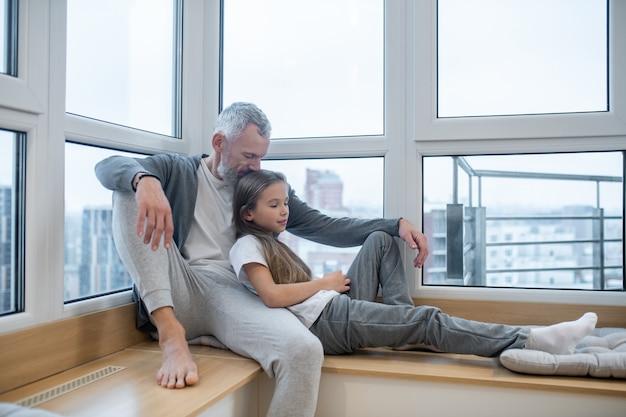 家族の時間。娘と一緒に窓際に座っているお父さん