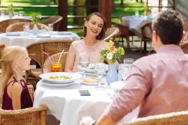 Время для семьи. сияющая привлекательная женщина, проводящая время с семьей, обедая вместе