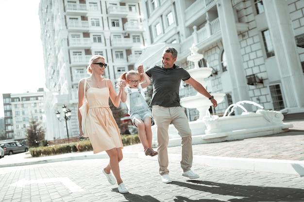 가족 시간. 쾌활한 남편과 아내는 도시 거리를 걷고 있는 손을 잡고 어린 딸을 들어올립니다.