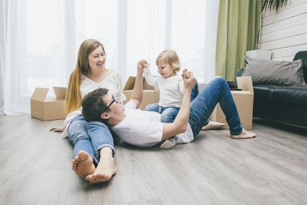 小さな赤ちゃんと一緒に美しい幸せな若い家族が箱を持って新しい家に移動します