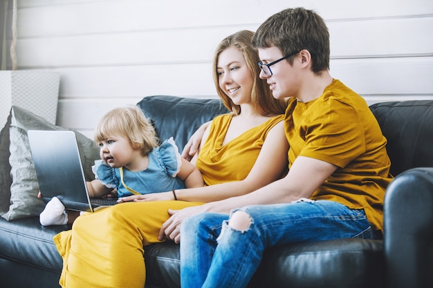 家でラップトップで作業している小さな子供と一緒に幸せな若い美しい家族