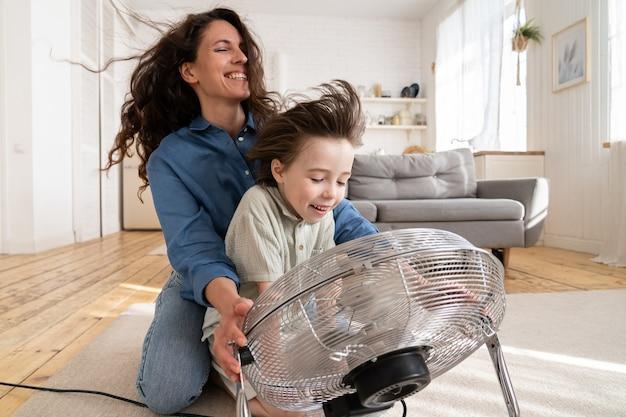Семья вместе молодая мама и сын дошкольного возраста смеются, сидя у вентилятора, дует прохладный ветер в лицо