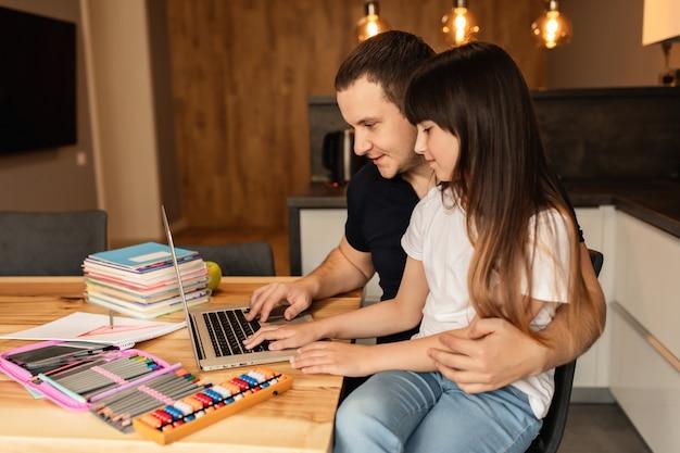 가족 관계, 온라인 학습. 아버지와 딸이 노트북을 사용하여 집에서 숙제를