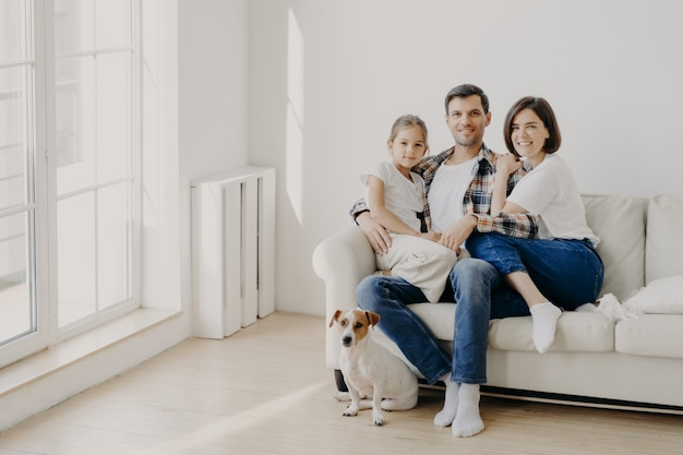Family, togetherness and relationship concept. happy man embraces daughter and wife, sit on comfortable white sofa in empty room, their pet sits on floor, make family portrait for long memory