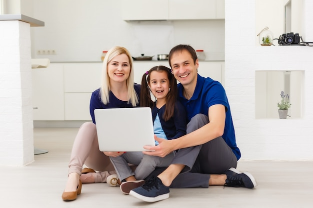 Family top view sitting on floor using laptop computer in her room at home