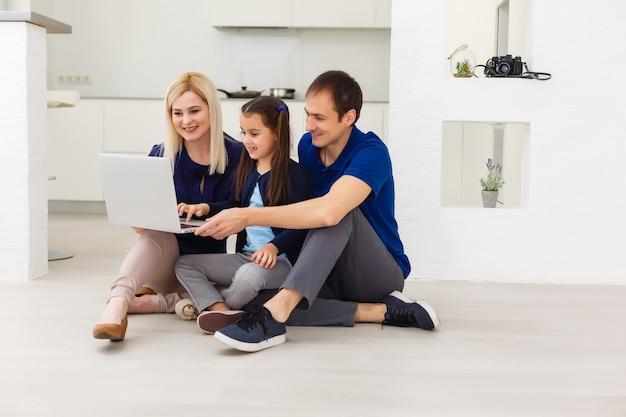 집에 있는 그녀의 방에서 노트북 컴퓨터를 사용하여 바닥에 앉아 있는 가족 최고 전망