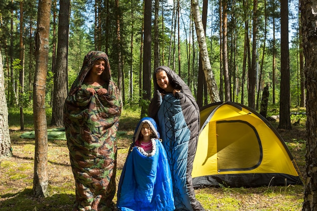 Family of tourists from a father, mother and little daughter pose in sleeping bags near a tent. family outdoor recreation, domestic tourism, camping, hiking equipment. pupated like caterpillars-humor