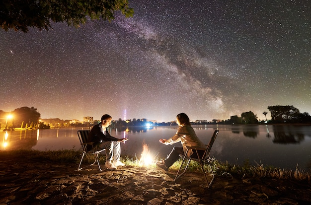 Family tourists man and woman sitting on chairs on a lake shore, warming hands on bonfire, enjoying evening sky full of stars and milky way above still water and city lights on background.