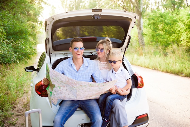 Family, transport, road trip and people concept - happy man and woman with little child travel.