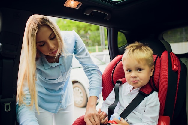 Family, transport, road trip and people concept - happy woman fastening child with safety seat belt in car