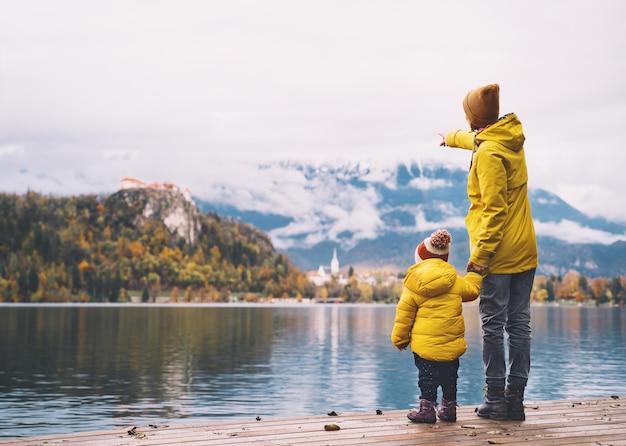 Семейное путешествие по европе мать и ребенок в желтых плащах, глядя на бледское озеро в словении