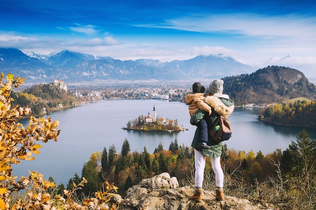 家族旅行ヨーロッパ。ブレッド湖を見ている息子と母。ヨーロッパのスロベニアの秋または冬。背景に城と山々があるブレッド湖のカトリック教会と島の平面図。