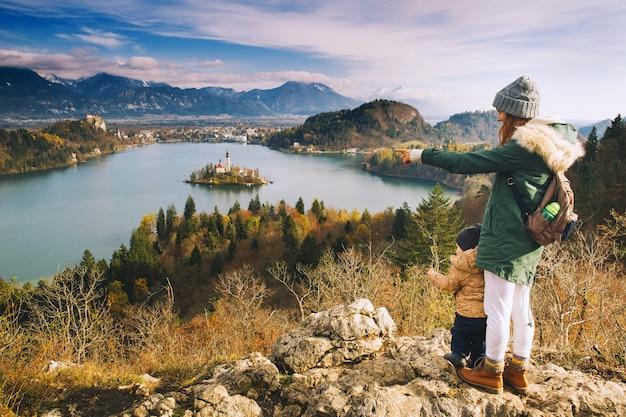 家族旅行ヨーロッパスロベニアヨーロッパのブレッド湖の秋または冬を見ている息子と母