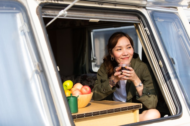 Family travel trip by caravan car on beautiful vacation. young asian woman in caravan with white coffee cup in morning