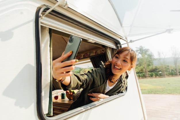 Family travel trip by caravan car on beautiful vacation. young asian woman selfie with smartphone in caravan with white coffee cup in morning
