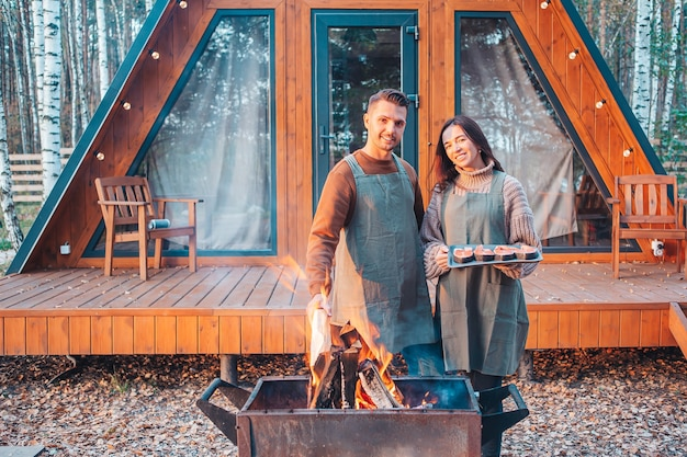 Family of two at autumn warm day grill outdoors