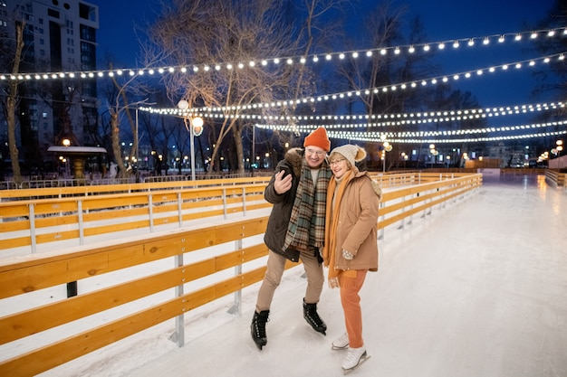 Family of two making selfie portrait on mobile phone while skating on skating rink in winter day