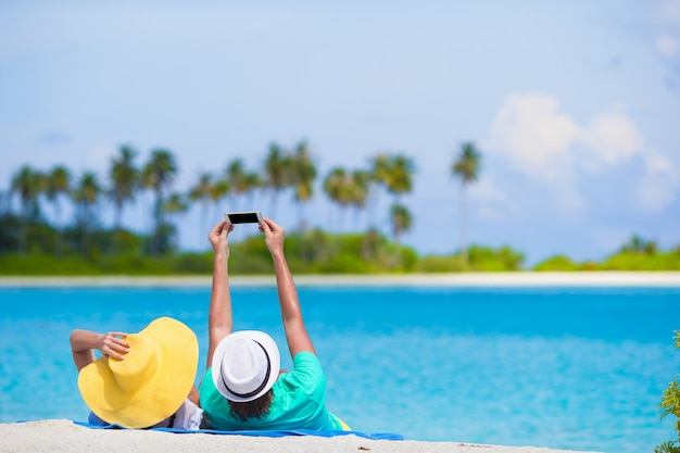 Family of two making a selfie with cellphone on beach