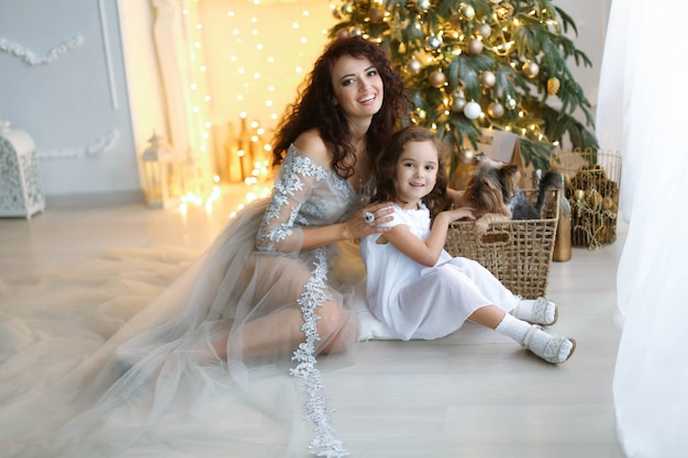 A family of two people mom and daughter in white dresses are sitting on the floor under the new year tree.