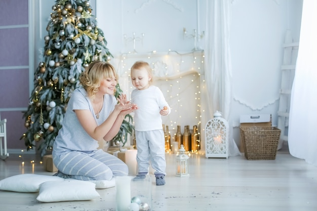 Family of two people mother and little girl at home on the background of a fireplace and a christmas tree.