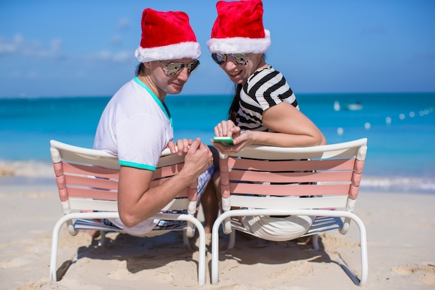 Family of two in santa hats sitting on beach chair