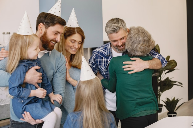Family and two their daughters have a celebration of grandmothers birthday adult son hugging his mother