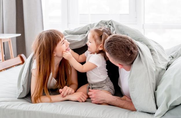 침대에서 담요 아래 가족