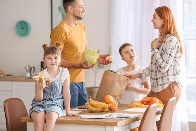 Семья распаковывает свежие продукты с рынка на кухне