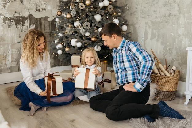 Семья распаковывает подарки возле украшенной елки. мать, отец и ребенок с новогодними подарками утром готовы открыть и отпраздновать