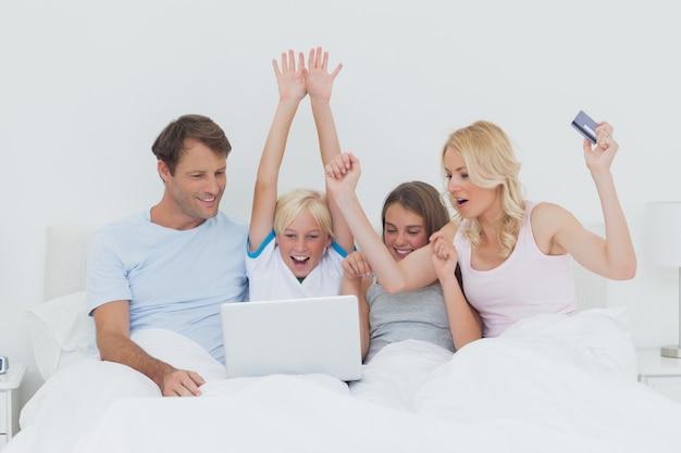 ベッドでラップトップを使用している家族
