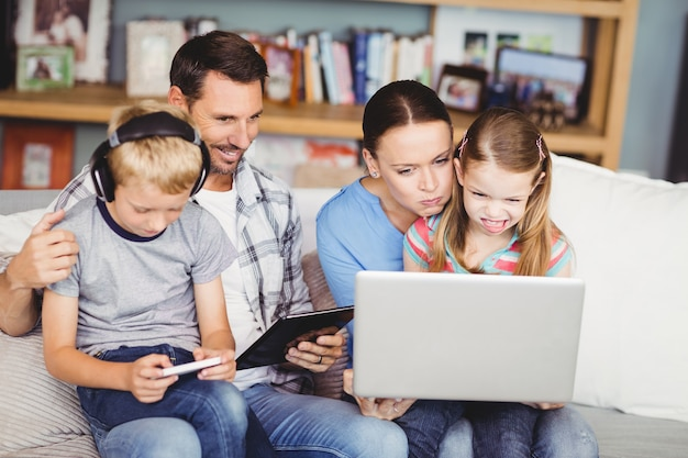 Family using technologies on sofa