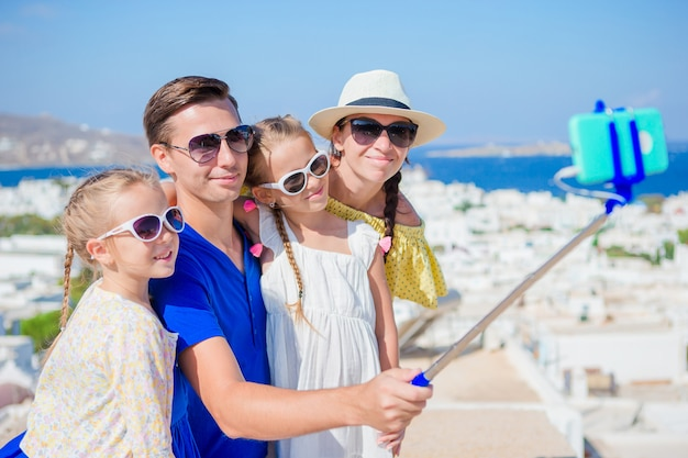 Family vacation in europe. parents and kids taking selfie photo in mykonos town in greece