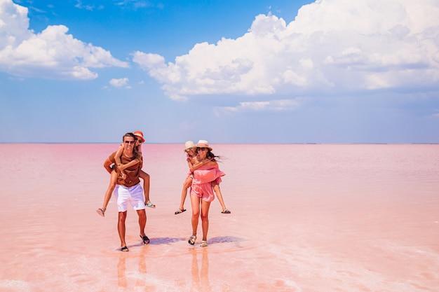 Семейный отдых. счастливые родители с двумя детьми на розовое соленое озеро в солнечный летний день. изучение природы, путешествий, семейного отдыха.