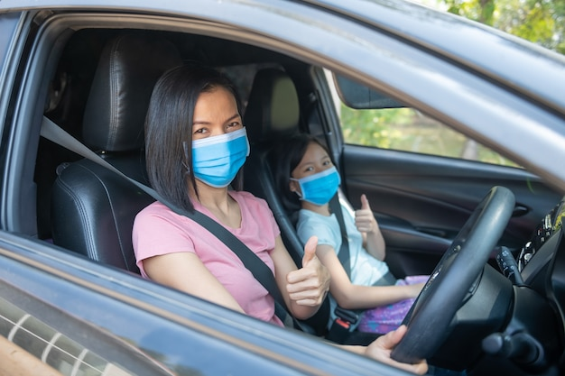가족 휴가 휴가, 코로나 바이러스 covid-19 및 얼굴 마스크, 어머니는 아이 소녀 딸을 위해 패브릭 얼굴 마스크를 착용했습니다. 새로운 정상적인 안전을 유지하십시오. 자동차로 여름 타기.