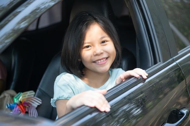 家族での休暇、車での遠征中の幸せな家族、娘が横に座っている間に車を運転する母親、母親と娘が旅行している。夏の自動車乗り。