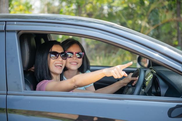 가족 휴가 휴가, 차를 타고 여행하는 행복한 가족, 옆에 앉아있는 딸, 엄마와 딸이 여행하는 동안 차를 운전하는 엄마. 자동차로 여름 타기.