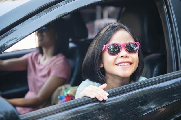 Vacanze in famiglia, famiglia felice in viaggio in macchina, mamma che guida l'auto mentre sua figlia è seduta accanto, mamma e figlia stanno viaggiando. giro estivo in automobile.