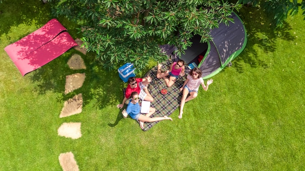Семейный отдых в кемпинге с высоты птичьего полета сверху, родители и дети отдыхают и весело проводят время в парке, палатке и туристическом снаряжении под деревом, семья в лагере на открытом воздухе концепции