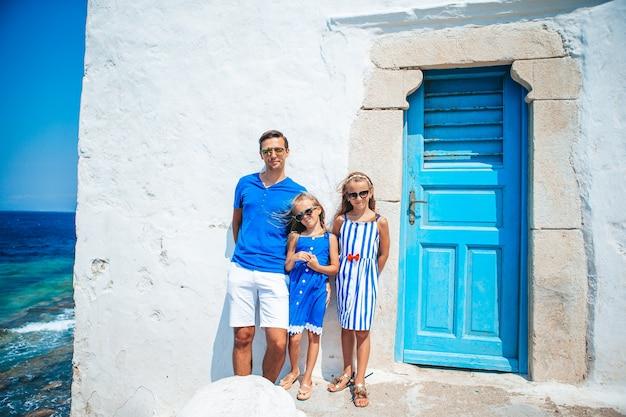 Семейный отдых в европе. отец и дети фон город миконос в греции