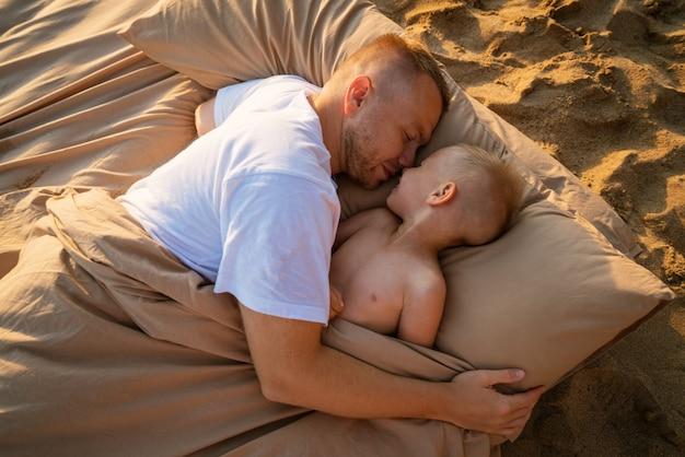 여름에 모래 해변에서 가족 휴가 아빠와 아들은 베이지색 침대 시트에 에어 매트리스에 누워 있습니다...