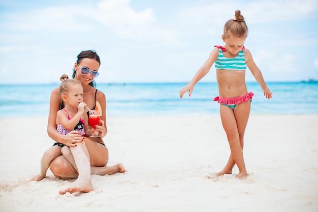 Семейный отдых. мать и маленькие девочки в отпуске на пляже