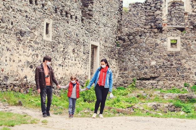 Семейный отдых. родители с сыном, носить маски на открытом воздухе. семейная поездка в старый замок во время пандемии.