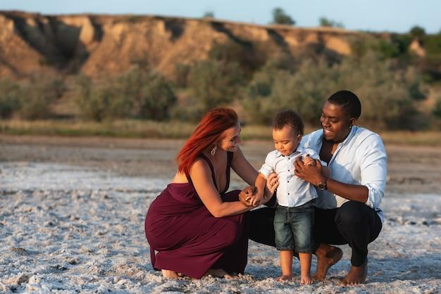 家族での休暇の肖像画。幼児の子供と笑顔の親。美しい夏の日にビーチでリラックスした若い混血家族