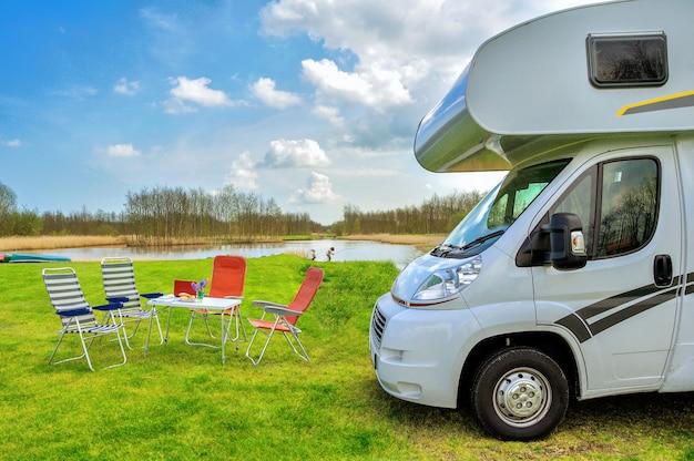 家族での休暇、rv(キャンピングカー)旅行の概念、キャンピングカー旅行、休日のキャンプ場でテーブルと椅子
