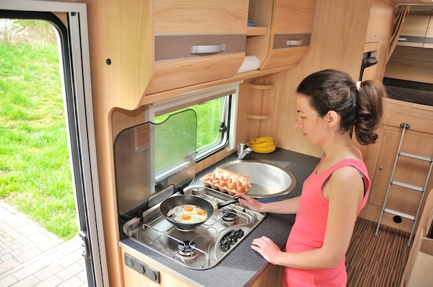Family vacation, rv holiday trip, travel and camping, happy smiling woman cooking in camper, motorhome interior